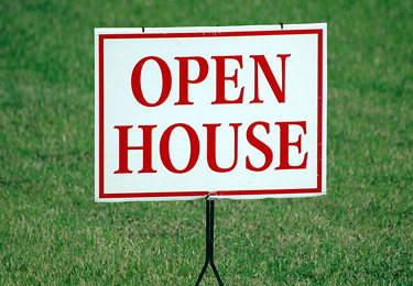 An open house sign against a green lawn.